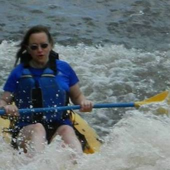 A woman on a sit on top kayak in a river.